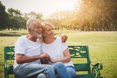 Höga par som har romantiker och, kopplar av tid i parkerar arkivfoton