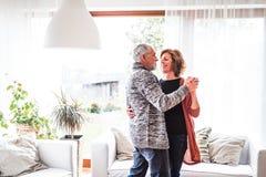 Höga par som hemma kopplar av och att dansa royaltyfria bilder