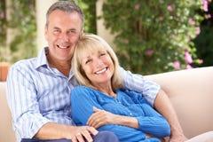 Höga par som hemma kopplar av på sofaen Royaltyfria Bilder