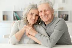 Höga par som hemma skrattar Fotografering för Bildbyråer