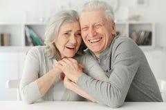 Höga par som hemma skrattar Arkivbild