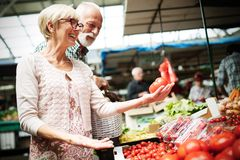Höga par som köper nya grönsaker och frukter på den lokala marknaden fotografering för bildbyråer
