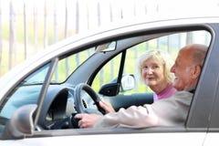 Höga par som kör bilen Arkivfoto