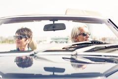 Höga par som kör en konvertibel klassisk bil Arkivfoton