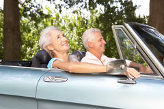 Höga par som kör i en sportbil Royaltyfria Bilder