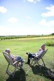 Höga par som kopplar av i stolar på solig dag Fotografering för Bildbyråer