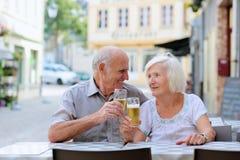 Höga par som kopplar av på det friakafét Arkivfoton