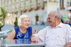 Höga par som kopplar av på det friakafét Royaltyfri Fotografi