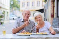 Höga par som kopplar av på det friakafét Royaltyfria Bilder