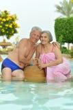 Höga par som kopplar av på pölen Royaltyfri Foto