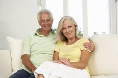 Höga par som kopplar av på Sofa At Home Together Arkivfoto
