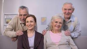 Höga par som kramar och ler på kameran, familjstående, samhörighetskänsla lager videofilmer