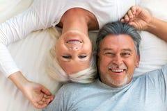 Höga par som ligger i säng royaltyfria bilder