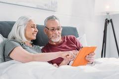 Höga par som ligger i säng och tillsammans använder minnestavlan arkivfoton