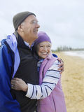 Höga par som omfamnar på stranden Royaltyfria Foton