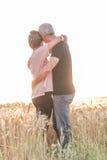Höga par som omfamnar sig i ett vetefält, solljuseffekt Arkivbild