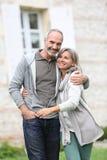 Höga par som omfamnar sig i trädgård Fotografering för Bildbyråer