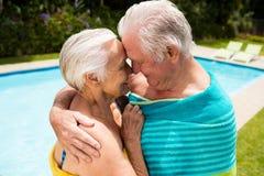 Höga par som omfamnar sig på poolsiden Arkivfoton