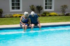 Höga par som påverkar varandra med de på poolsiden Arkivfoton
