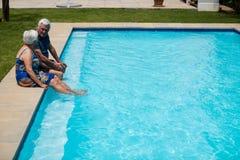 Höga par som påverkar varandra med de på poolsiden Royaltyfria Foton