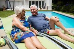 Höga par som påverkar varandra med de på vardagsrumstol Royaltyfri Bild