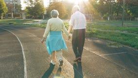 Höga par som promenerar det rinnande spåret Arkivfoto