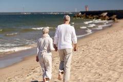 Höga par som promenerar sommarstranden arkivfoto