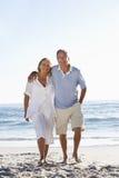 Höga par som promenerar stranden Arkivbilder