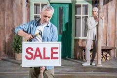 Höga par som säljer deras hus, inhyser till salu begrepp Royaltyfria Bilder