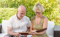 Höga par som ser en bilderbok, arkivfoto