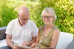 Höga par som ser en bilderbok, arkivbilder