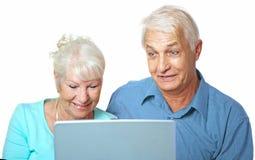 Höga par som ser lyckliga på bärbara datorn Royaltyfria Bilder