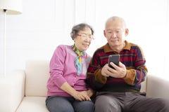 höga par som ser mobiltelefonen arkivbild