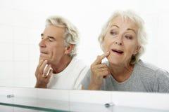 Höga par som ser reflexioner i spegeln för tecken av att åldras Royaltyfri Foto