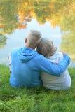 Höga par som sitter nära sjön Arkivfoton