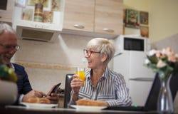 Höga par som skrattar i kök arkivbild