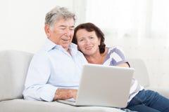Höga par som skrattar, medan genom att använda bärbara datorn Arkivfoton