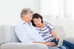 Höga par som skrattar, medan genom att använda bärbara datorn Royaltyfri Foto