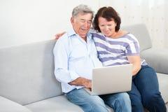 Höga par som skrattar, medan genom att använda bärbara datorn Arkivbilder