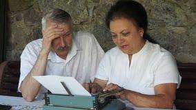 Höga par som skriver traditionell post vid skrivmaskinen stock video