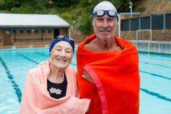 Höga par som slås in i handduk på poolsiden Royaltyfria Bilder