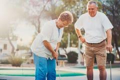 Höga par som spelar mini- golf som tycker om en pensionerad livsstil royaltyfria bilder