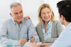 Höga par som talar med en konsulent Arkivfoto