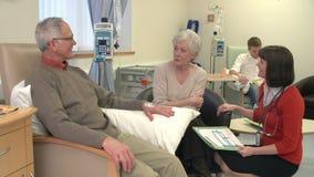 Höga par som talar till kvinnlig doktor During Chemotherapy arkivfilmer