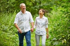 Höga par som tar en gå i skog fotografering för bildbyråer