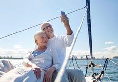 Höga par som tar selfie vid smartphonen på yachten royaltyfri fotografi