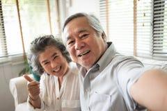 Höga par som tar selfiefoto med smartphonen arkivbilder