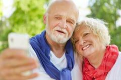 Höga par som tar selfieståenden med smartphonen Royaltyfria Bilder
