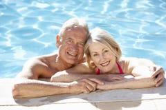 Höga par som tillsammans kopplar av i simbassäng Royaltyfria Foton