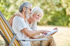 Höga par som tillsammans läser en bok arkivfoton